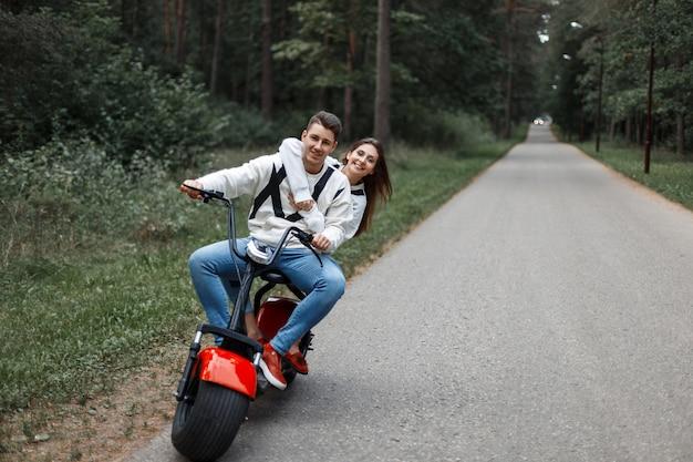 Verliebtes paar, das ein elektrofahrrad auf der straße fährt