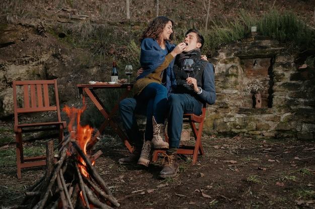 Verliebtes paar, das ein romantisches abendessen im freien mit lagerfeuer hat. frau auf den beinen des mannes füttert ihn.