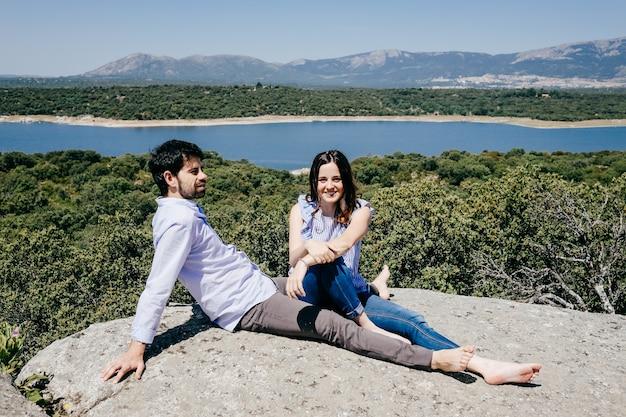 Verliebtes paar, das einen schönen frühlingstag auf dem land mit blick auf einen großen see genießt