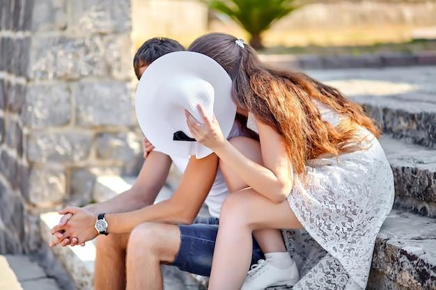 Verliebtes paar, das hinter weißem weiblichem hut auf der steintreppe in der altstadt küsst. junger mann und frau umarmen sich. sonniger sonnentag