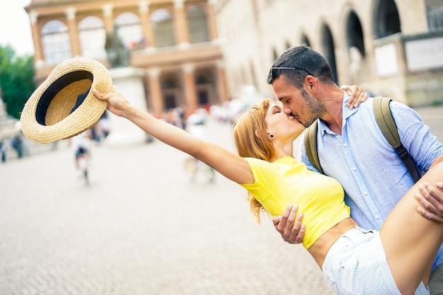 Verliebtes paar, das im urlaub in der stadt lacht und küsst. mann, der freundin im freien umarmt.