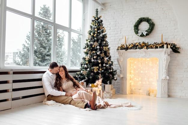 Verliebtes paar, das in der nähe des großen fensters und des weihnachtsbaums im dekorierten studio sitzt und sich umarmt