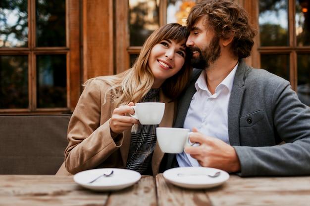 Verliebtes paar, das in einem café sitzt, kaffee trinkt, sich unterhält und die zeit miteinander genießt. selektiver fokus auf tasse.