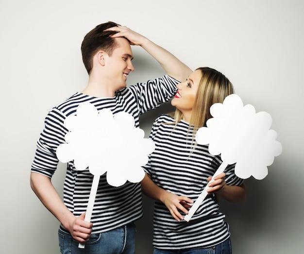 Verliebtes paar, das leere papiere auf stöcken hält