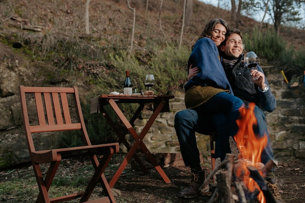 Verliebtes paar, das nach einem romantischen picknick am horizont schaut. dame auf den beinen des mannes umarmt und trinkt wein.