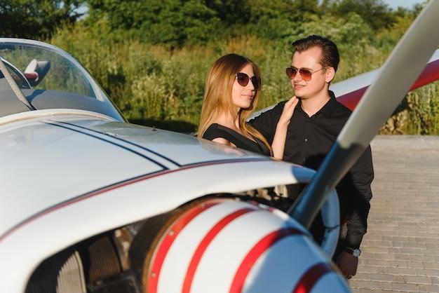 Verliebtes paar, das nahe privatflugzeug umarmt