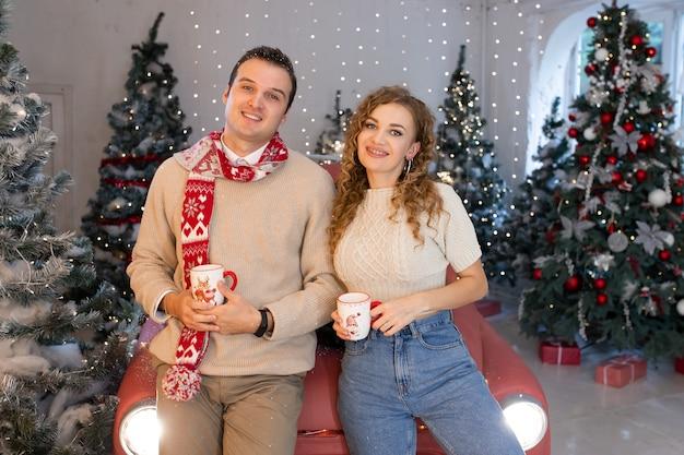 Verliebtes paar, das nahe schön geschmücktem weihnachtsbaum lächelt und den weihnachtszauber genießt.