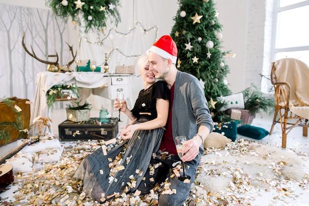 Verliebtes paar, das nahe weihnachtsbaum sitzt, der neues jahr mit champagner und konfetti feiert