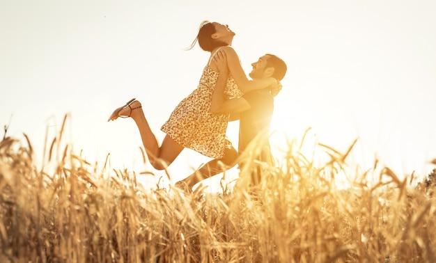Verliebtes paar, das spaß in einem weizenfeld hat
