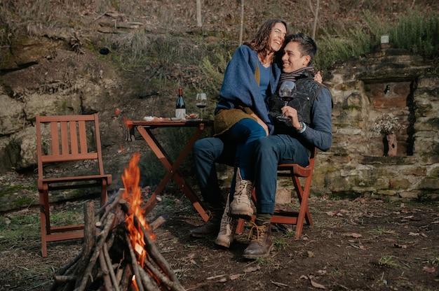 Verliebtes paar, das wein trinkt und spaß in einem garten mit feuer hat. leute, die am tisch sitzen und frau auf den beinen des mannes