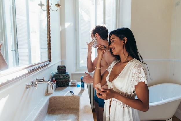 Verliebtes paar, das zeit zusammen im haus verbringt. romantische momente im badezimmer