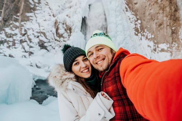 Verliebtes paar in den bergen. liebhaber machen im winter ein selfie vor dem hintergrund eines wasserfalls.