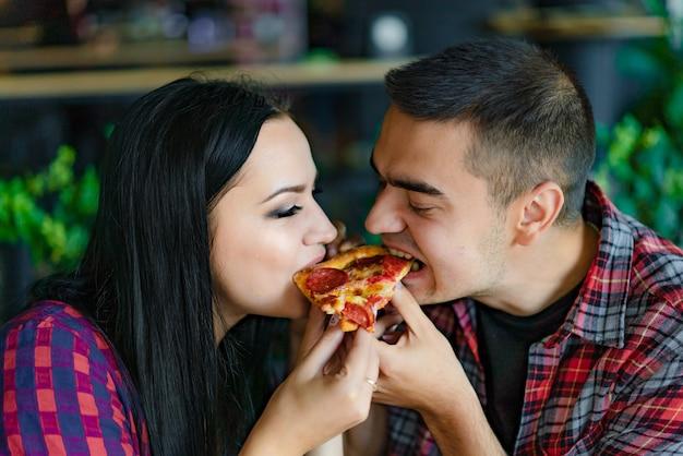 Verliebtes paar isst ein stück heiße pizza