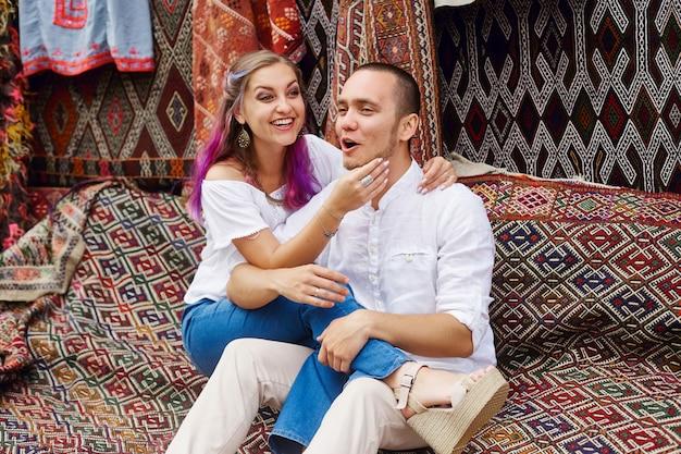 Verliebtes paar kauft auf einem orientalischen markt in der türkei einen teppich und handgemachte textilien. umarmungen und fröhliche gesichter von männern und frauen