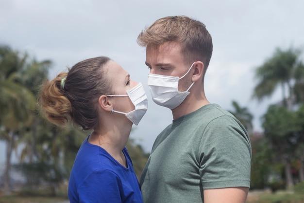 Verliebtes paar, mann und frau küssen sich und schauen sich in der schützenden medizinischen maske auf gesicht an. konzept der umweltverschmutzung. guy, mädchen gegen chinesische pandemie coronavirus, virus, grippe-schutz