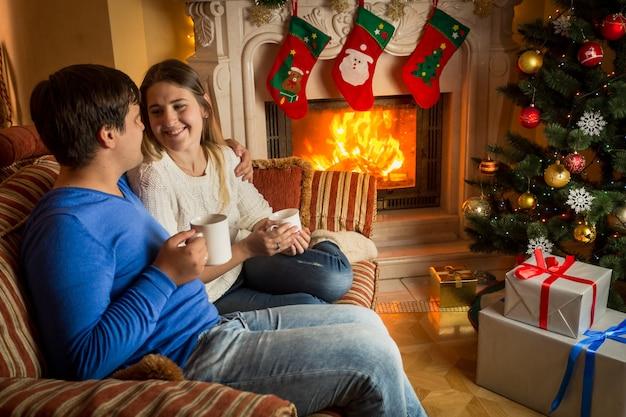 Verliebtes paar trinkt tee auf dem sofa am brennenden kamin, der für weihnachten dekoriert ist