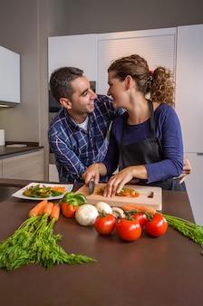 Verliebtes paar umarmt und bereitet gesundes gemüse in der küche zu. modernes familienlebensstilkonzept.