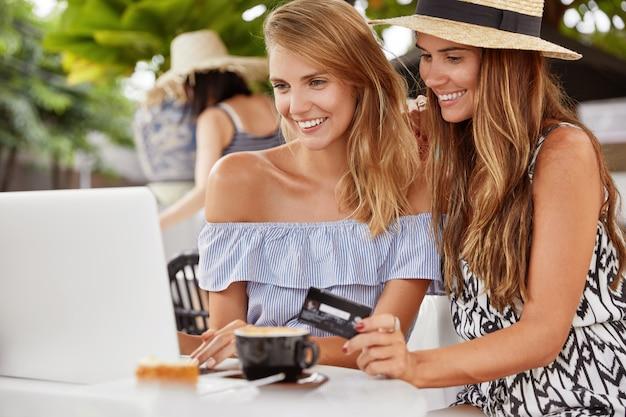 Verliebtes weibliches paar macht online-einkäufe, freut sich über neue einkäufe, sieht glücklich aus in einem laptop. online-zahlung oder e-commerce