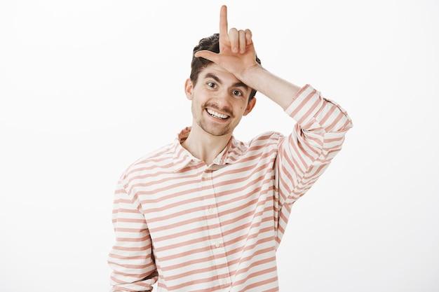 Verlierer bleiben zu hause. glücklicher fröhlicher gutaussehender europäischer mann mit schnurrbart und bart, der l wort mit der hand über der stirn macht und breit lächelt