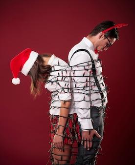 Verlierer nerd paar verheddern sich in weihnachtslichtern