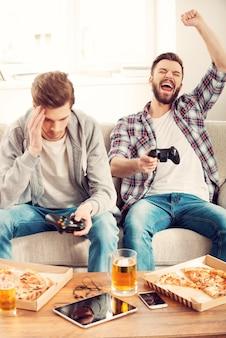 Verlierer und gewinner. zwei junge männer, die videospiele spielen, während sie auf dem sofa sitzen