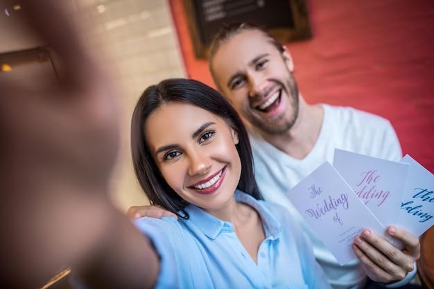 Verlobtes paar mit hochzeitseinladungen in einem café