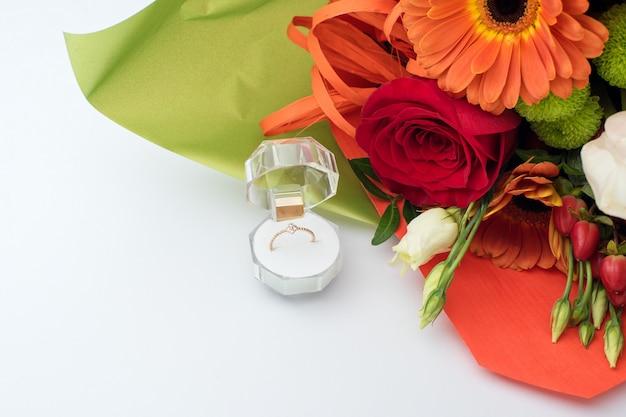 Verlobungsring in einer geschenkbox mit hellem blumenstrauß. das angebot zu heiraten. geschenk zum valentinstag. heiratsantrag für geliebte frau. symbol für liebe und ehe.