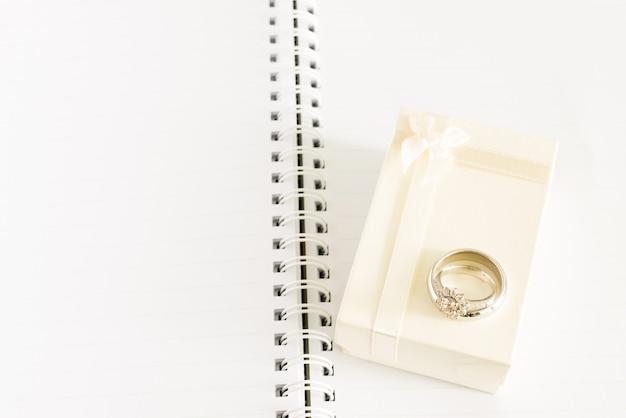 Verlobungsring und geschenkbox auf anmerkungsbuch