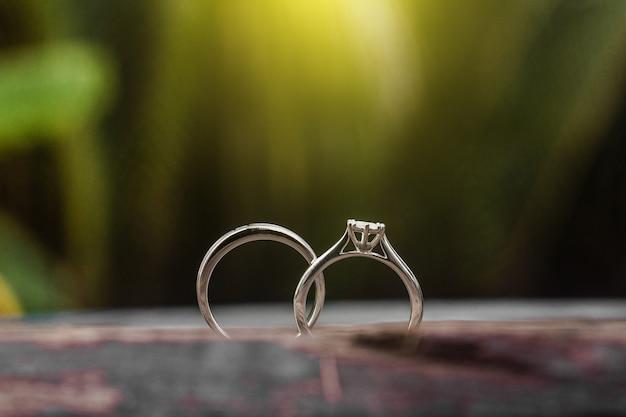 Verlobungsringe, eheringe für paare auf einem hölzernen hintergrund. für hochzeit, luxuriöse verlobung diamantringschmuck