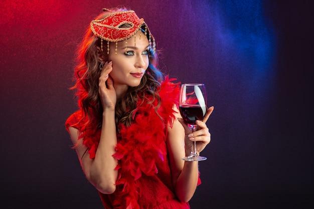 Verlockende frau in einer roten karnevalsmaske und -boa mit einem angehobenen glas wein, der weg schaut