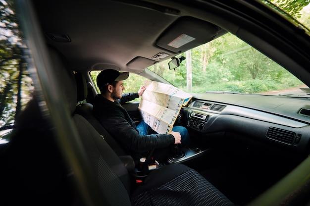 Verloren im waldjungen fahrer, der im auto beim halten der karte und beiseite schauen sitzt