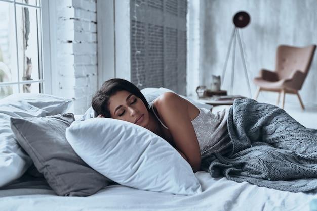 Verloren in einem tiefen schlaf. attraktive junge frau, die die augen geschlossen hält, während sie zu hause auf dem bett liegt