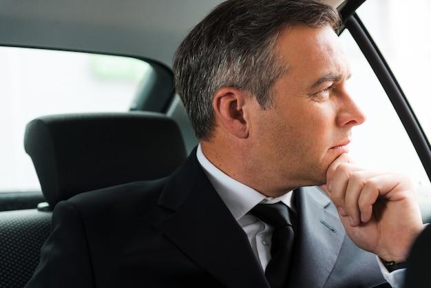 Verloren in geschäftlichen gedanken. nachdenklicher reifer geschäftsmann, der hand am kinn hält und wegschaut, während er auf dem rücksitz eines autos sitzt