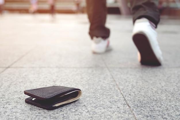 Verlorene brieftasche auf bürgersteig mit besitzer im hintergrund