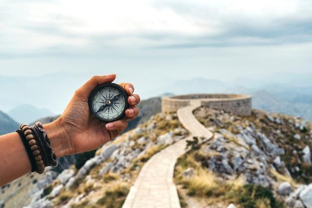 Verlorene frau auf dem berg, orientiert sich mit einem kompass. finde eine lösung.