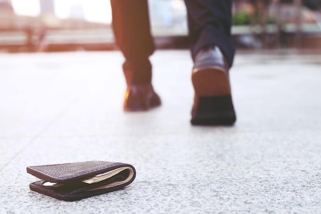 Verlorene lederbrieftasche mit verlorenem geld auf dem bürgersteig