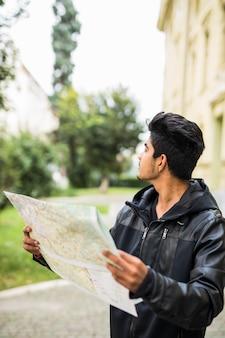 Verlorener indischer tourist, der stadtplan auf einer reise betrachtet