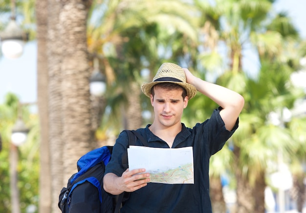 Verlorener tourist mit der tasche, die karte hält