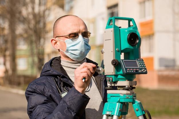Vermesser in einer maske arbeitet mit einer totalstation