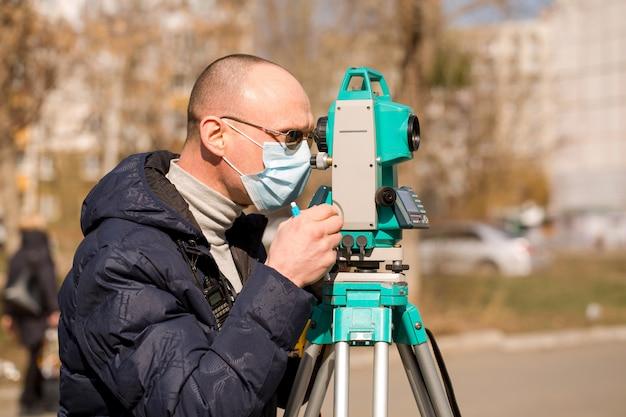 Vermesser in einer schutzmaske arbeitet mit einer totalstation