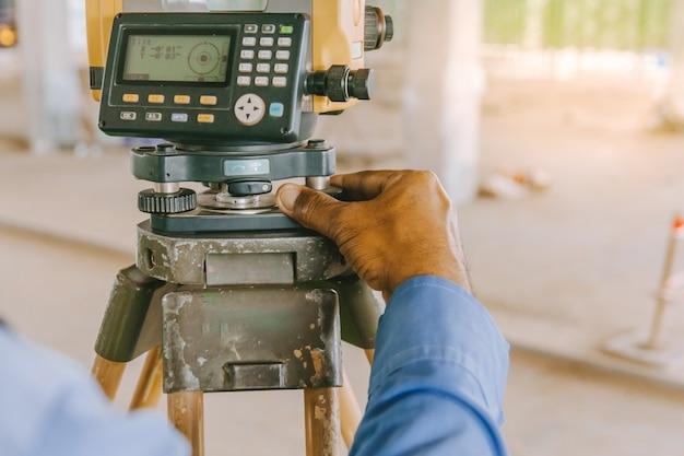 Vermessungsingenieurarbeitskraft, die das messen mit theodolitausrüstung an der baustelle macht.