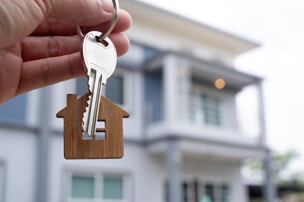 Vermieter entsperrt den hausschlüssel für neues zuhause. immobilienmakler, handelsvertreter.