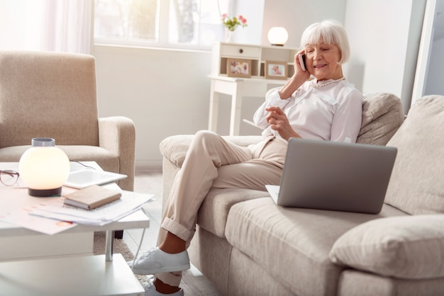 Vermisse dich. zierliche ältere dame, die auf dem sofa im wohnzimmer sitzt und mit ihrer freundin spricht und ein abendessen arrangiert