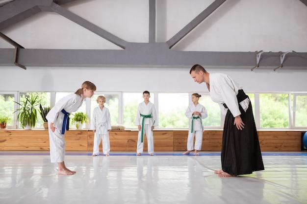 Verneige dich vor dem trainer. mädchen mit weißem kimono, das dem trainer vor dem aikido-training eine verbeugung gibt