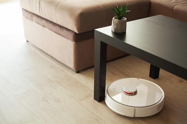 Vernetztes haus. staubsaugerroboter läuft auf holzfußboden in einem wohnzimmer.