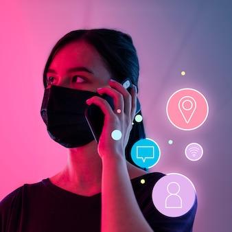 Vernetzung während der sozialen distanzierungsfrau, die maske trägt, die am telefon spricht