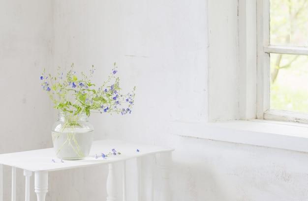 Veronica der wilden blumen im glas im weißen weinleseinnenraum