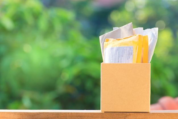 Verpacken des braunen paketkastens auf schönem natürlichem grünem hintergrund.