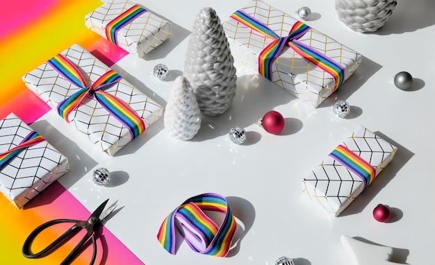 Verpacken von weihnachtsgeschenken in weißem papier mit regenbogenband in den lgbt-gemeinschaftsflaggenfarben