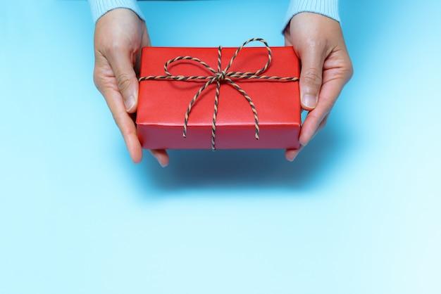 Verpackentagesladen, hand der jungen frau mit einem geschenkboxangebot zum empfänger